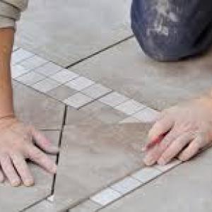 плиточник укладывает плитку на клей